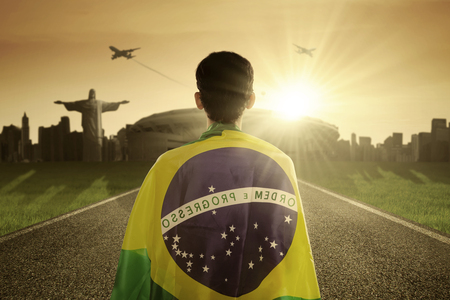 supporter: Backside of a man standing on the road with flag of Brazil, shot at sunrise time
