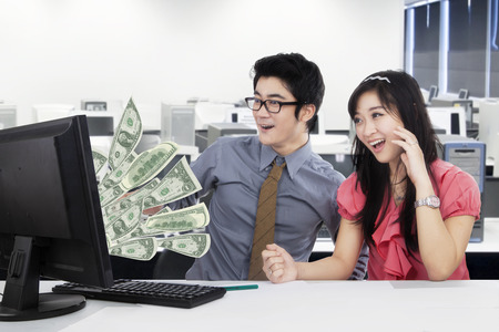 money business: Two Asian workers looks shocked while looking at the money on the computer, shot in the office