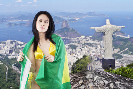 rio: Portrait of beautiful female model wearing bikini and using Brazilian flag for covering her body with Rio de Janeiro city background
