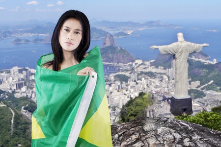 brazilian flag: Beautiful young girl using the Brazilian flag for covering her body with Rio de Janeiro city background