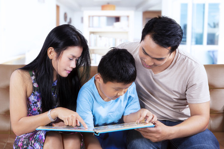 storybook: Two young parents and their son read a storybook together while sitting on the couch at home