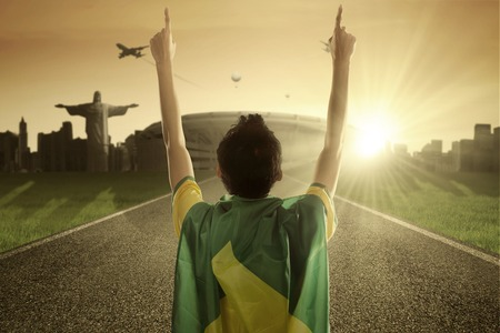 supporter: Image of a young man standing on the road with Brazilian flag and raises his hands