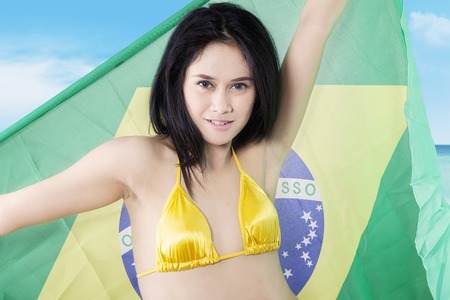 brazil beach swimsuit: Beautiful young woman wearing swimsuit on the beach and holding Brazilian flag Stock Photo