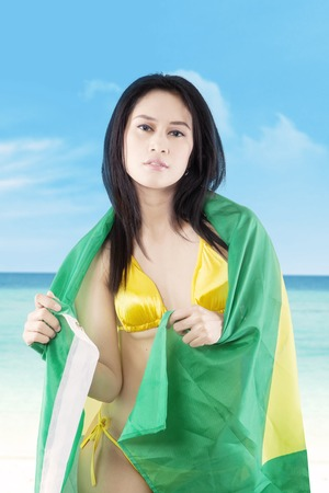 brazil beach swimsuit: Portrait of pretty young girl wearing bikini on the coast while holding Brazilian flag