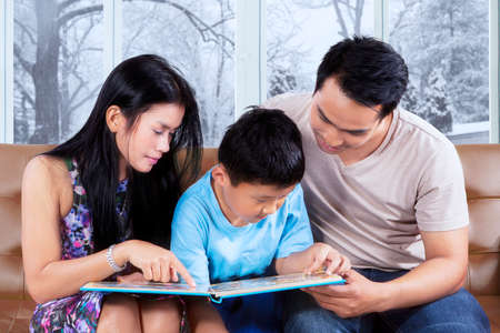 storybook: Photo of two happy parents and their son sitting on the sofa while reading storybook with winter background on the window