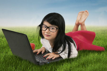girl lying: Beautiful little girl wearing glasses and using notebook computer while lying on the grass at the field
