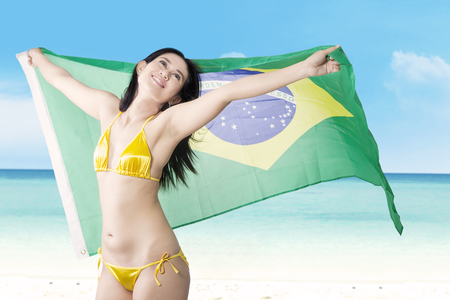 brazil beach swimsuit: Portrait of sexy young girl standing on the beach while wearing bikini and holding Brazilian flag