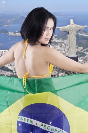 rio: Backside of sexy girl smiling at the camera while holding flag of Brazil with Rio de Janeiro city background Editorial