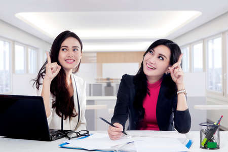 idea: Two cheerful businesswoman get good idea while working together with laptop and documents on the desk in office Stock Photo