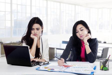 Twee vrouwelijke werknemers vervelen omdat overwerkt tijdens de vergadering op het bureau in het kantoor