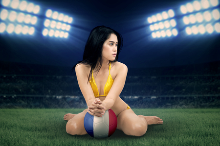 football european championship: Sexy female soccer fan wearing bikini while sitting at the field and holding a ball with flag of France