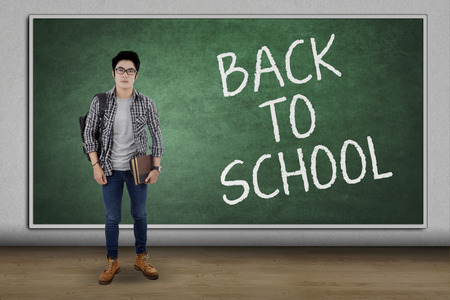 school boy: Male high school student standing in the classroom with text of Back To School on the blackboard Stock Photo