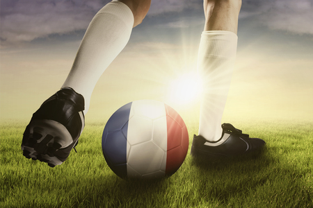 football shoes: Foot of soccer player wearing football shoes while playing a ball on the field with national flag of France Stock Photo