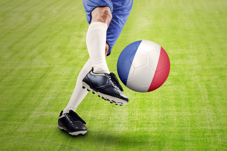 penalty flag: Foot of a soccer player kicking a ball with a France flag at field.