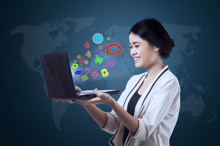 happy workers: Beautiful businesswoman looking at laptop screen with colorful media icons. Shot with world map background