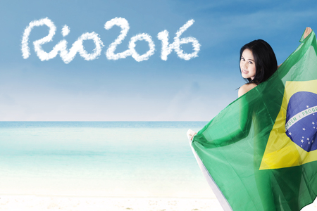 brazil beach swimsuit: Beautiful female model smiling at the camera while holding Brazilian flag with text of Rio 2016 on the beach Editorial