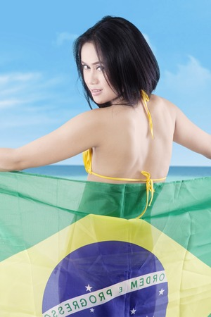 brazil beach swimsuit: Backside of young woman wearing bikini on the coast while holding Brazilian flag