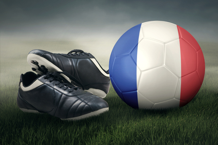 soccer shoes: Close up of a soccer ball with France flag and two soccer shoes on the meadow.