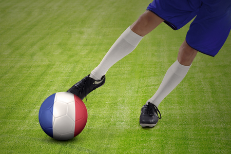 penalty flag: Close up of foot of soccer player exercises to kick a ball with a France flag at field. Stock Photo