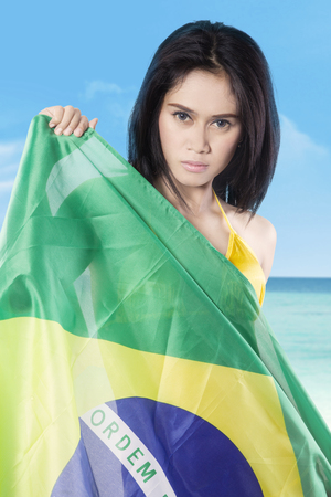 brazil beach swimsuit: Pretty girl standing on the beach while wearing bikini and holding the national flag of Brazil Stock Photo