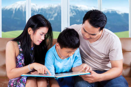 storybook: Picture of two young parents and their child sitting on the couch while reading storybook at home