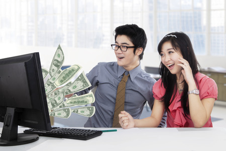 earn money: Picture of two young businesspeople earn money online and look at the money on the monitor Stock Photo