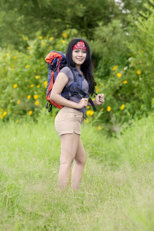 travel woman: Portrait of beautiful woman walking in the forest while hiking and carrying bag