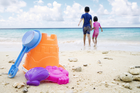 Imagen de los juguetes de playa de los niños dos niños jugando en la playa tropical