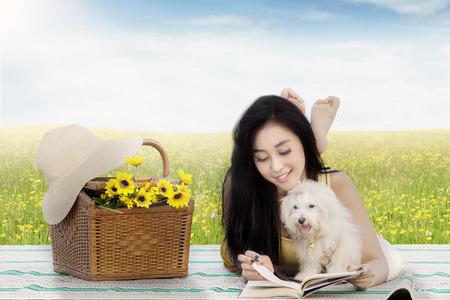 campo de flores: Retrato de la mujer bastante joven que lee un libro con el perro maltés y cesta de picnic en la estera en el prado