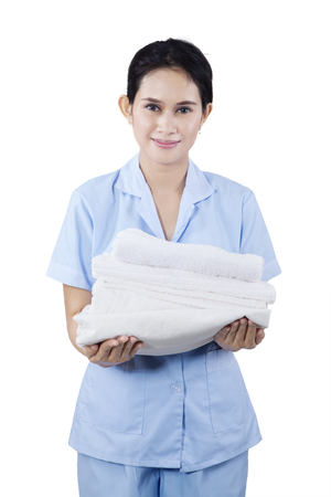 white towels: Portrait of a maid woman holding towels and smiling at camera. Isolated on white background