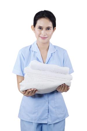 sirvientes: Retrato de una mujer de limpieza que sostiene las toallas y sonriendo a la cámara. Aislado en el fondo blanco