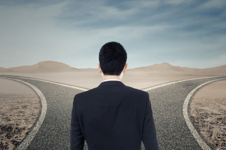 choose a path: Businessman looking at two highway and confused to choose the right way Stock Photo