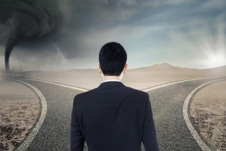 Backside di uomo d'affari confuso in piedi sulla strada, mentre appare confuso di scegliere la strada giusta