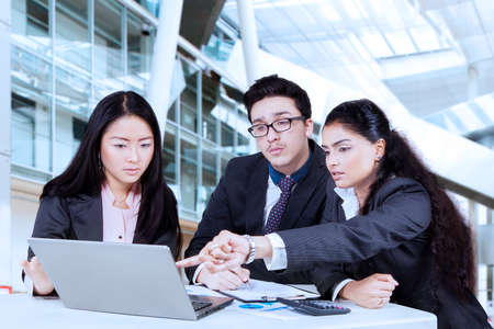 group meeting: Young businesswoman pointing on the laptop to show document at her partners