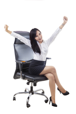 happy workers: Successful businesswoman sitting on the chair and raising hands up, isolated on white background Stock Photo