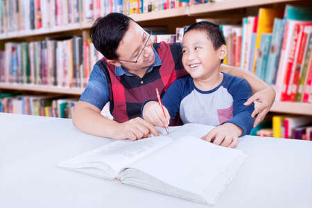 schoolwork: Portrait of male elementary student doing schoolwork with his tutor in the library