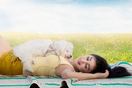 mujer con perro: Imagen de una bella mujer joven que duerme en el prado con un perro maltés Foto de archivo