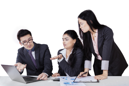 subordinates: Young female leader looking at the laptop with her two subordinates show the problem