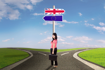 sceptic: Brexit concept. Young businesswoman standing on the road with flag of UK and EU on the brexit signpost Stock Photo