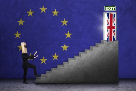 sceptic: Brexit concept. Businessperson with cardboard head walking on the ladder toward exit door with flag of England and EU