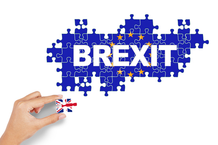 sceptical: Brexit concept. Hand holding puzzle piece with flag of Great Britain and European Union
