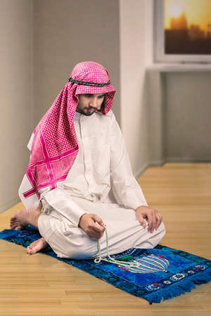 muslim pray: Young Arabian person doing dhikr while sitting on the carpet and holding beads at home