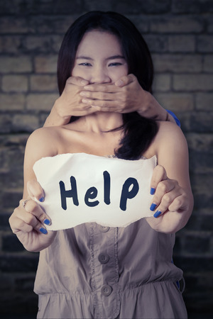 kidnapped: Portrait of scared teenage girl kidnapped by someone while holding a paper with a help text Stock Photo