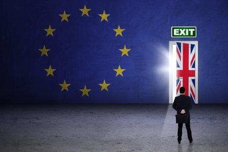 Brexit concept. Jonge zakenman op zoek naar exit deur met de nationale vlag van Engeland en de EU