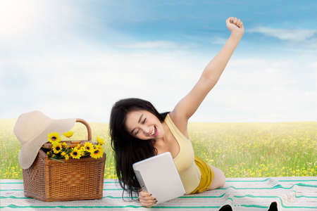 raise hand: Portrait of a cheerful girl lying on the meadow while using a digital tablet and raise hand Stock Photo