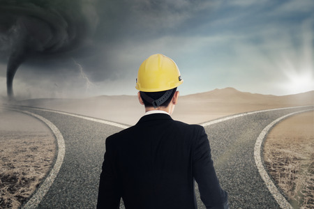 tormenta: El hombre de negocios de pie en la carretera mientras llevaba casco y mirando dos carreteras con tormenta y la luz del sol Foto de archivo