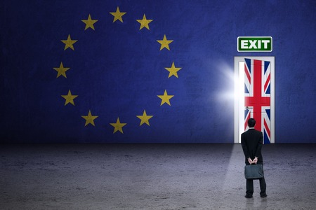EU: Brexit concept. Male worker wearing formal suit and looking at brexit door with flag of UK and EU Stock Photo