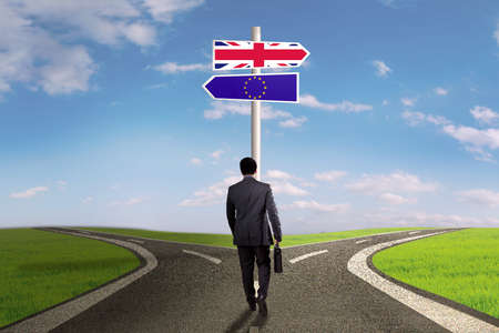 briefcase: Brexit concept. Businessman walking on the street with flag of England and European Union on the signpost