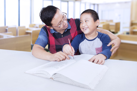 Study Desk: Male teacher guide a little boy to study and doing schoolwork, shot in the classroom