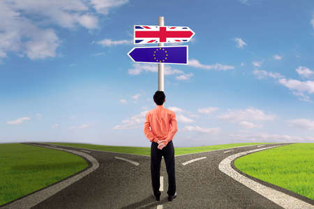 sceptic: Brexit concept. Young man standing on the road while looking at signpost with flag of Great Britain and European Union Stock Photo